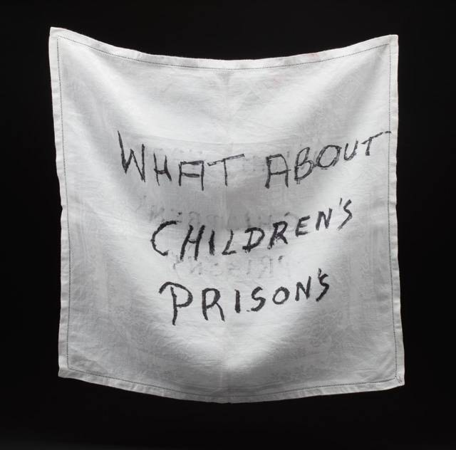 """A white napkin in-scripted with """"What about children's prisons"""""""
