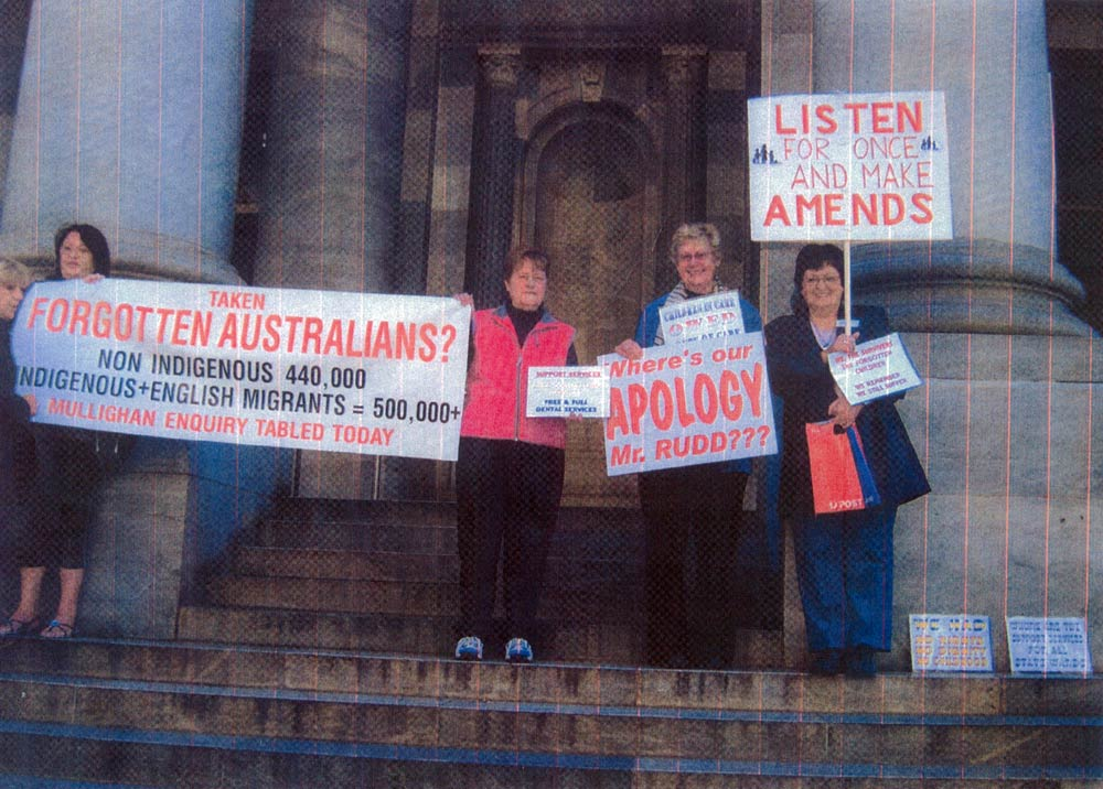 Four women standing in front of a large building holding signs and banners about Forgotten Australians